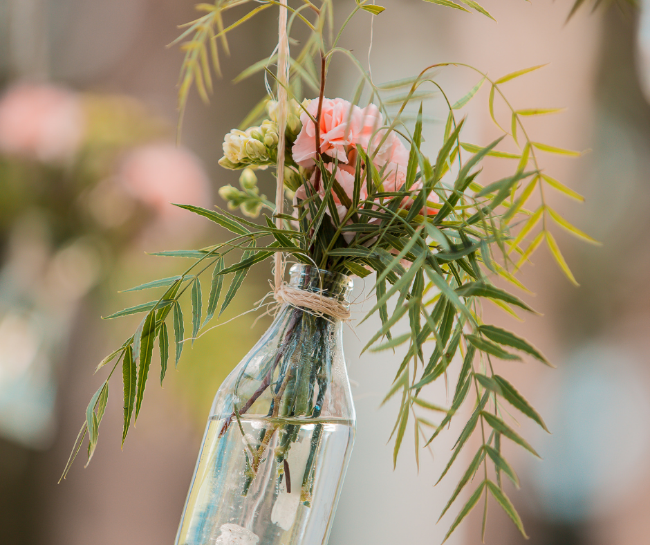 a bunch of flowers in a hanging vase diy dollar store wedding decor pieces.